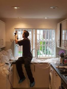 iks locksmith fitting a colapsible grille in london